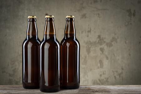 botellas vacias: Tres botellas de cerveza fría de hielo en una fila sobre el fondo gris muro de hormigón Foto de archivo