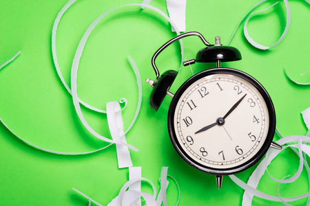 teared paper: Old vintage alarm clock standing on the green paper surface with pieces of teared paper