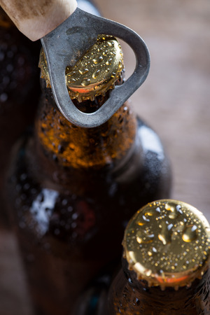dew cap: Brown ice cold beer bottles with water drops and old opener Stock Photo