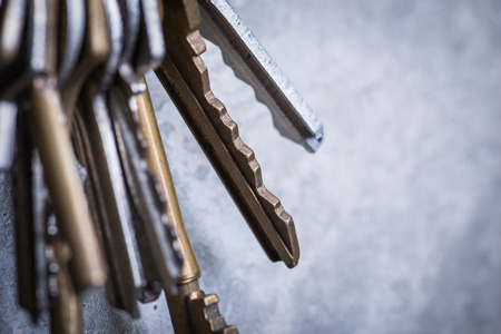 locksmith: A bunch of old worn keys hanging on the screw on the grey concrete wall Stock Photo