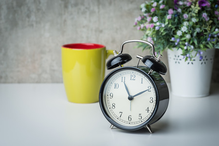 night table: Vintage alarm clock on a night table with flowers and coffee mug