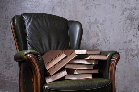 cosy: Cosy green leather armchair with books in front of the wall Stock Photo