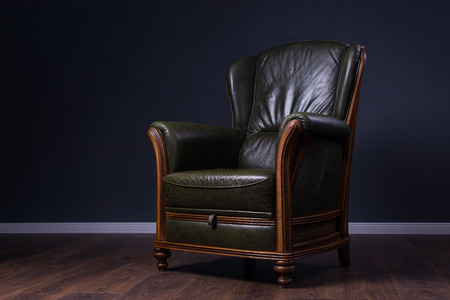 cosy: Cosy green leather armchair in front of the wall
