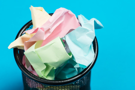 blue bin: Colorful paper in a garbage bin on a blue surface Stock Photo