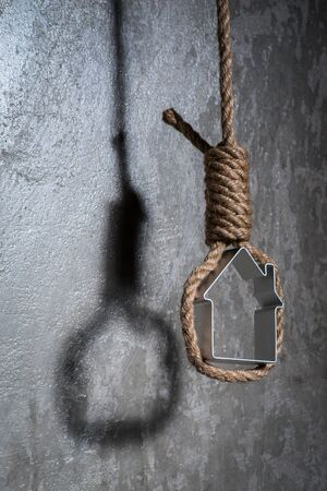 noose: Small house framed with hangmans noose hanging over the grey concrete wall
