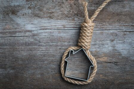 noose: Small house framed with hangmans noose on the old wooden surface