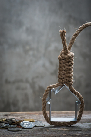 noose: Hangmans noose with house and coins on brown wooden surface Stock Photo