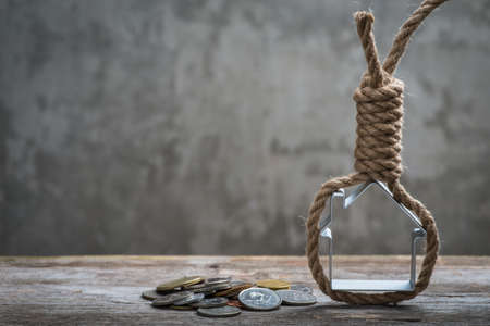Hangmans noose with house and coins on brown wooden surface Stock Photo