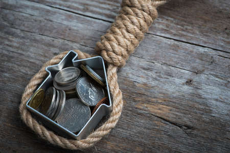 slipknot: Hangmans noose with house and coins on brown wooden surface Stock Photo