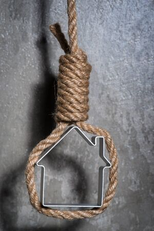 Small house framed with hangmans noose hanging over the grey concrete wall