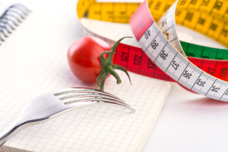 metering: Fork, notepad, metering tape and tomato over the white background, isolated