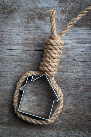 Small house framed with hangmans noose on the old wooden surface