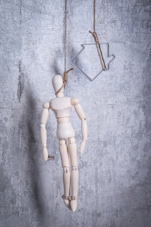 wooden figure: Wooden figure of human and house hanging in the hangmans loop Stock Photo