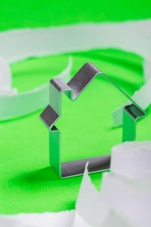 teared paper: Funny metal house standing on a green surface with teared paper pieces