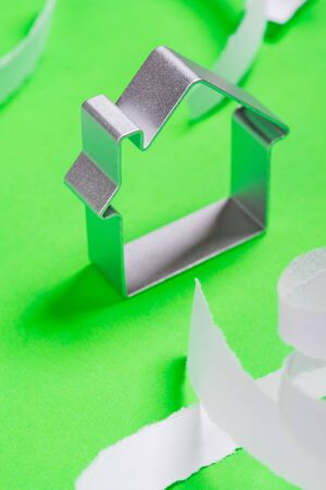 teared: Funny metal house standing on a green surface with teared paper pieces