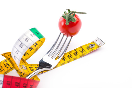 weight loss plan: Fork, tomato and metering tape over the white background, isolated Stock Photo