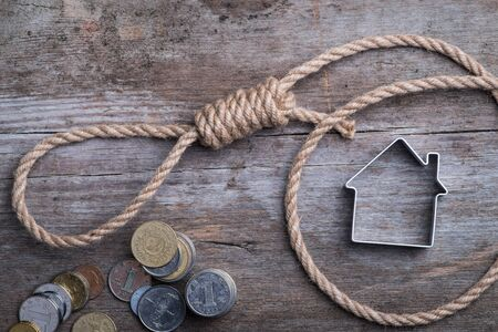 Hangmans noose with house and money on brown wooden background Stock Photo