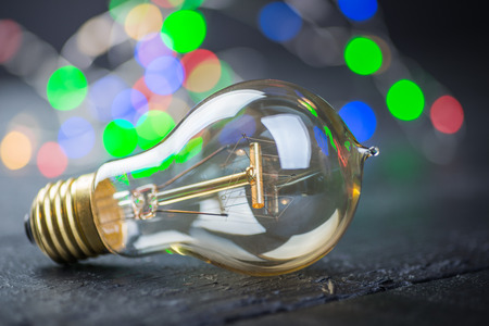 tungsten: Vintage tungsten bulb on a black wooden table with colorful lights at the background