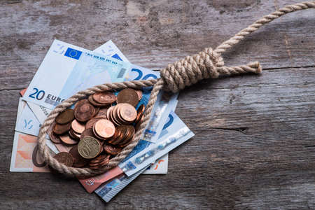 Hangman's noose with money on brown wooden background