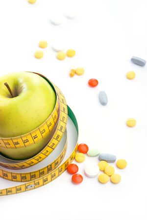 overeat: Fresh green apple with measuring tape and pills on white table