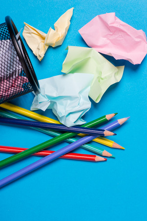Small black trash bin with color pencils and crumpled color paper inside over the blue background Stock Photo