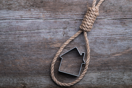 Small house framed with hangmans noose on brown wooden background