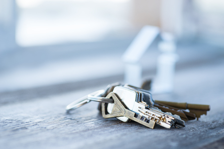 A bunch of vintage keys with metal house on the wooden table 写真素材