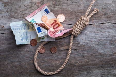 Hangmans noose with money on brown wooden background