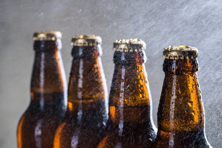 dew cap: Ice cold beer bottles with drops of dew over the grey background