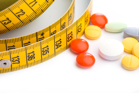 overeat: Measuring tape and pills on white table