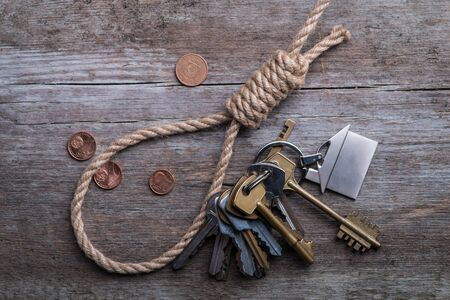 slipknot: Hangmans noose with house, keys and money on brown wooden background Stock Photo