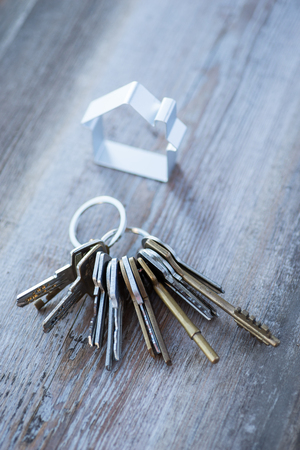 A bunch of vintage keys with metal house on the wooden table Фото со стока