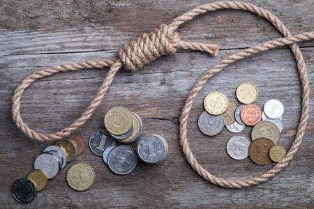 noose: Hangmans noose with money on brown wooden background