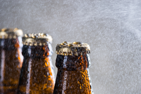 Ice cold beer bottles with drops of dew over the grey background