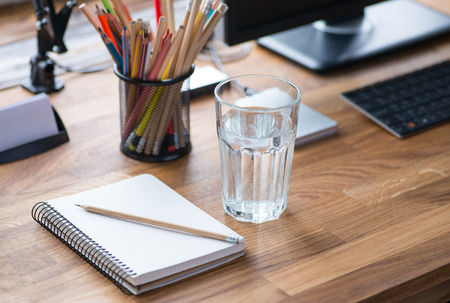 oficina desordenada: lugar de trabajo luz y acogedor con lápices de colores y un vaso de agua Foto de archivo