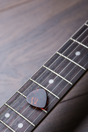 frets: Guitar frets with strings and mediator on dark brown surface Stock Photo