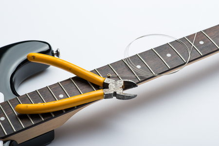 nippers: Guitar frets with string and yellow nippers Stock Photo