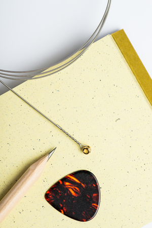 yellow notepad: Yellow notepad with pencil, string and mediator on white surface