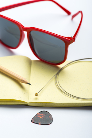 yellow notepad: Yellow notepad with pencil, sunglasses, string and mediator on white surface