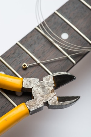 frets: Guitar frets with string and yellow nippers Stock Photo