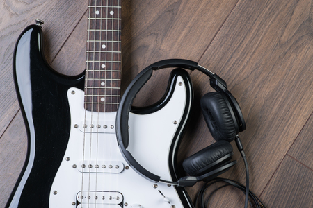 riff: Electric guitar with headphones on a brown wooden floor Stock Photo