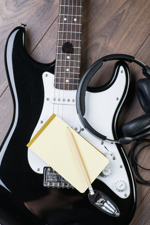 riff: Electric guitar with headphones, notedpad and pencil on a brown wooden floor Stock Photo