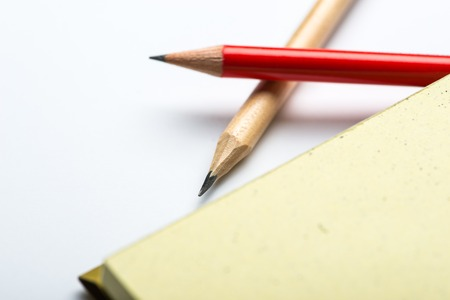 yellow notepad: Yellow notepad with two pencils on white surface Stock Photo