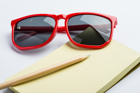 yellow notepad: Red sunglasses with yellow notepad and pencil on white surface