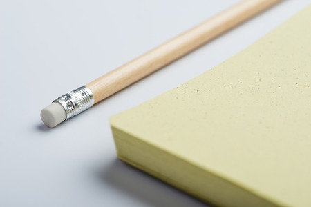 yellow notepad: Yellow notepad with pencil on white surface