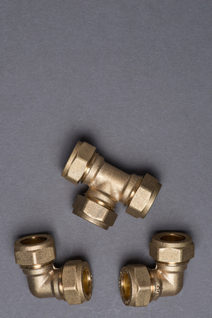 compression: Brass plumbing compression fittings on grey surface Stock Photo