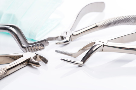 extraction: Pliers and extraction forceps on white surface
