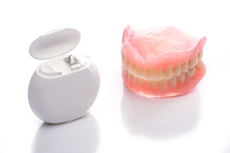 Teeth model with dental floss on white surface
