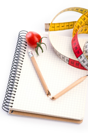 metering: Notebook with metering tape, pencil and tomatoes over white background Stock Photo