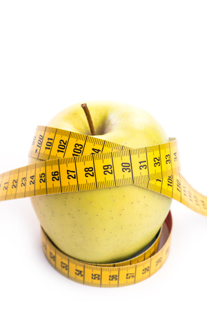 metering: Fresh and green organic apple with metering tape over white background